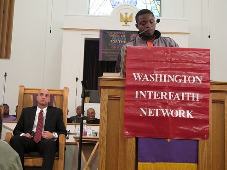 Youth leader speaks to crowd at March 2010 Action while Fenty looks uncomfortable in the background.